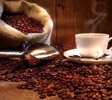 Skodelica kave ob vreči praženih zrn