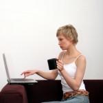 ženska s skodelico kave ob računalniku