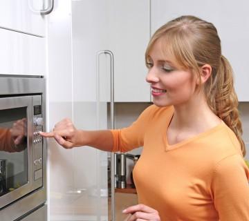 ženska kuha v mikrovalovni pečici