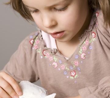 mala deklica odpira jogurt