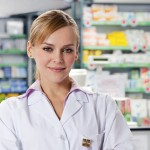 lekarničarka pred policami zdravil v lekarni