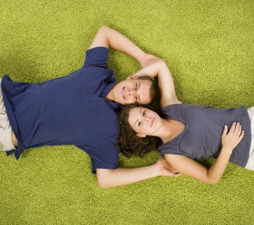 mlad par leži na zelenem tapisonu
