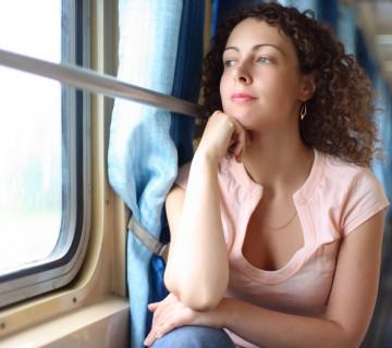 ženska na vlaku gleda skozi okno