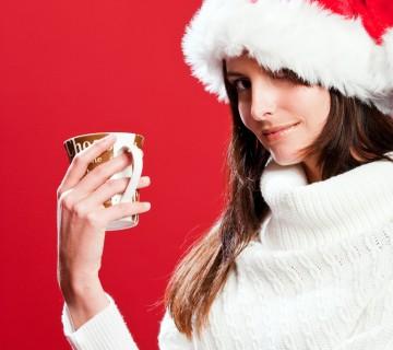 ženska z božično kapo in skodelico v roki