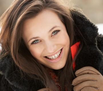 nasmejana ženska v zimskem plašču
