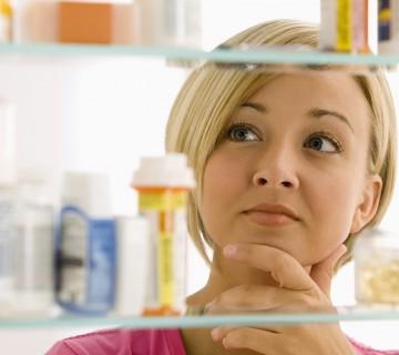 ženska gleda v omarico z zdravili
