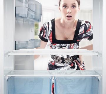 mlada ženska gleda v prazen hladilnik