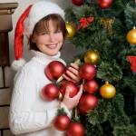 ženska z božično čepico drži rdeče okraske za drevesce