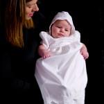 ženska drži dojenčka v krstnem oblačilu
