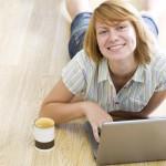 ženska z notesnikom in kavo leži na tleh