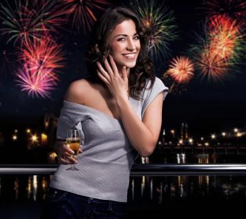 ognjemet v ozadju ženske s kozarcem šampanjca