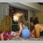 mama in hčeri gledajo ognjemet skozi okno