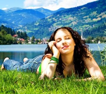 ženska leži v trevi, v ozadju jezero in hribi