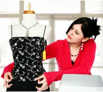 prodajalka namešča obleko na lutko