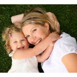nasmejani mami in malčica ležita v travi
