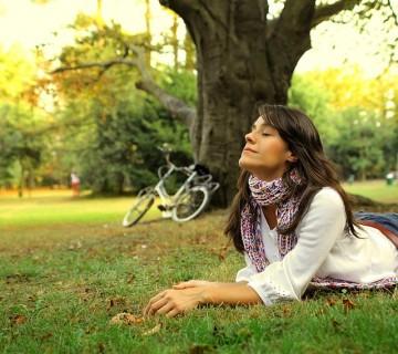 ženska v parku leži na zelenici
