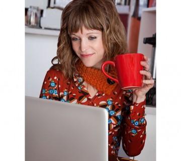 ženska pije čaj ob računalniku