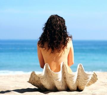 ženska na obali sedi v lupini školjke