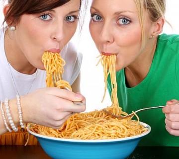 dve ženski jesta špagete z enega krožnika