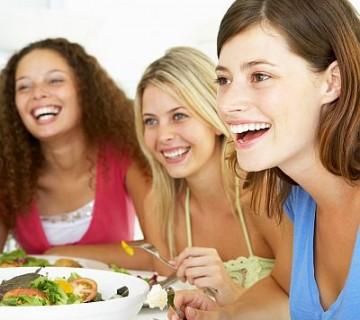 tri nasmejane ženske ob kosilu