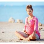 nosečnica sedi v pesku na obali