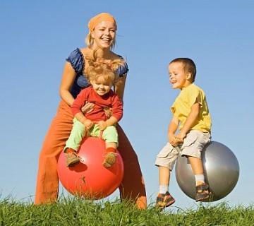 mama in dva otroka na soncu skačejo s skokicami