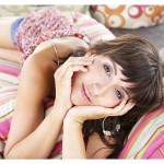 poletno oblečeno dekle leži na blazinah v senci
