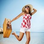ženska s slamnikom in kovčkom na plaži