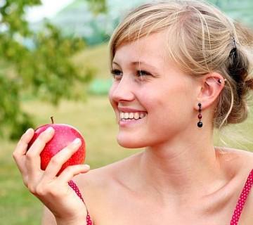 nasmejana ženska drži v roki jabolko
