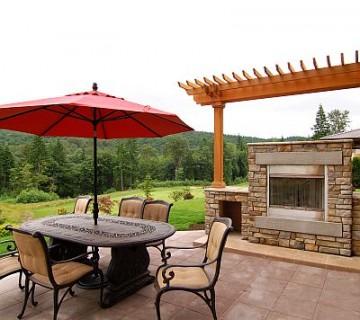 terasa z zunanjim kaminom, mizo, stoli in rdečim senčnikom
