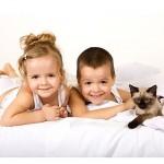 deklica, deček in mačka ležijo na postelji