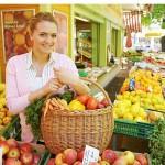 ženska na tržnici s košaro polno zelenjave