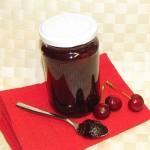 kozarec marmelade, žlica z marmelado in češnje