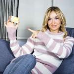 ženska drži v roki kartico in kaže nanjo s prstom