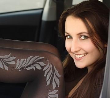 ženska sedi v avtu z dvignjenimi nogami, da se vidijo nogavice