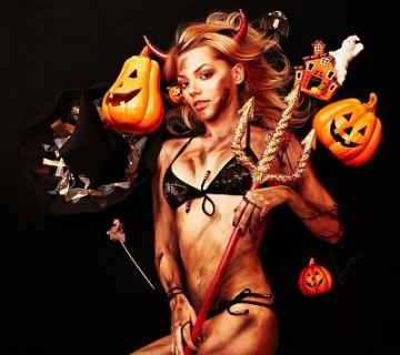 privlačna ženska v kopalkah, z rožički in rekviziti za noč čarovnic