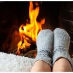 stopala v nogavičkah se grejejo ob prižganem kaminu
