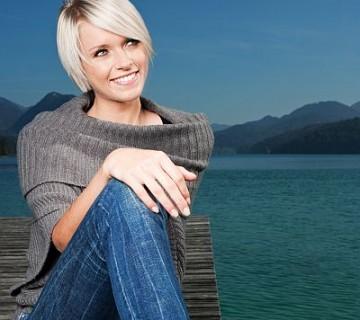 ženska v džinsu na pomolu jezera