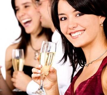 ženska s kozarčkom belega vina na zabavi