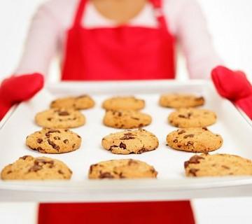 piškoti na pekaču, ki ga drži ženska