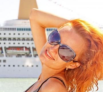nasmejana ženska s sončnimi očali in potniško ladjo v ozadju
