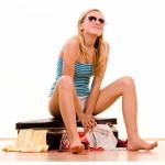 ženska z golimi nogami sedi na kovčku