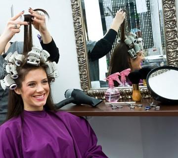 ženska z navijalkami pred ogledalom pri frizerju