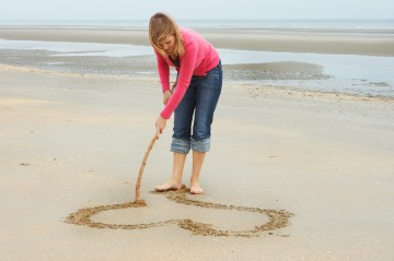 Young woman drawing a heart in the beach sand
