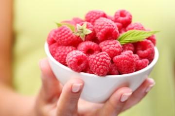 Crockery with raspberries in woman hand.